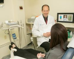 Dr. James Dores talking to a patient in the chair at Dores Dental in East Longmeadow, MA